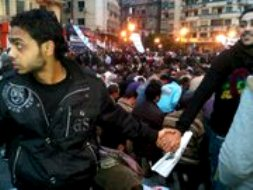 Egyptian Muslims kneel to pray in Tahrir Square, Christians link arms to protect them.
